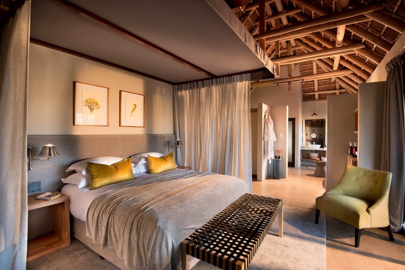 Bedroom suite interior with ensuite bathroom, all under thatch and wooden beams