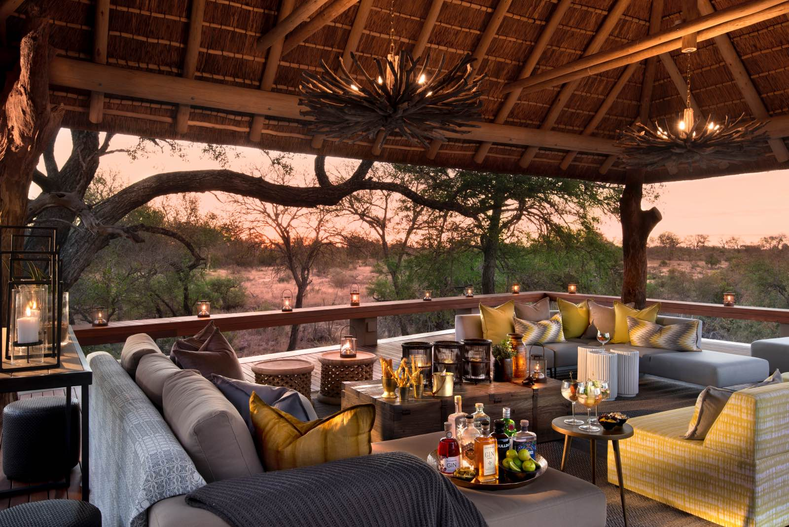 Lounge under thatch on a wooden deck with a view onto the surrounding bush