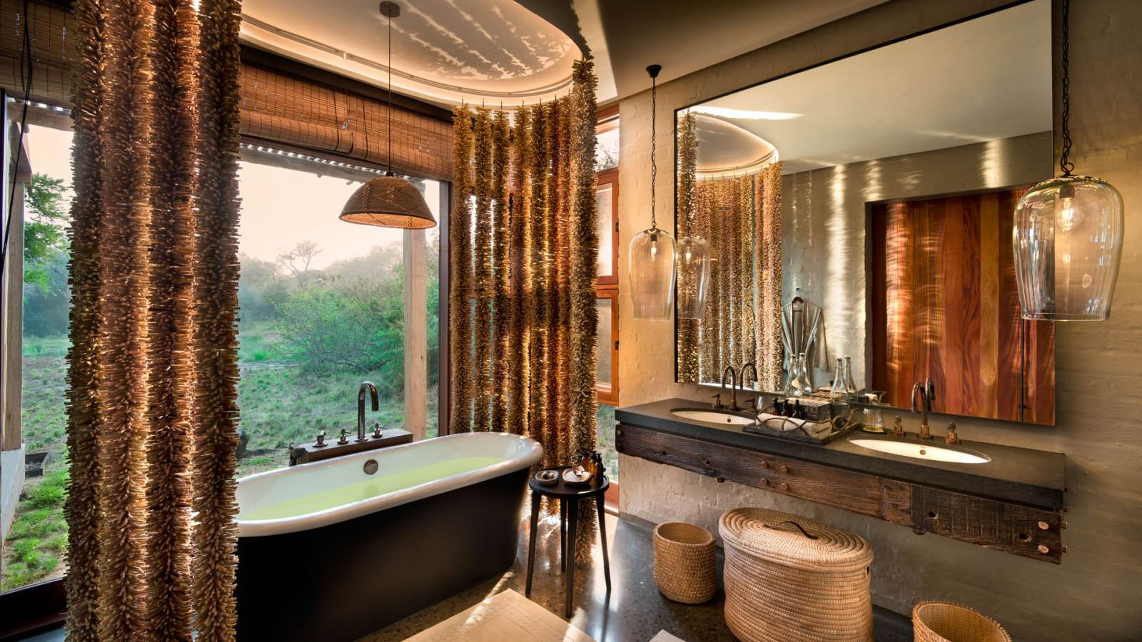 A bathtub with a view through big glass windows at Phinda Homestead