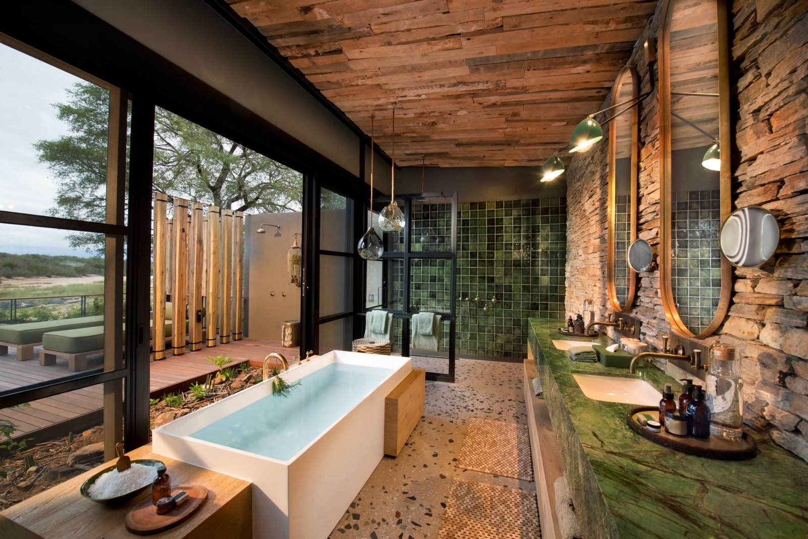 A bath with a view and an outdoor shower in en suite bathrooms