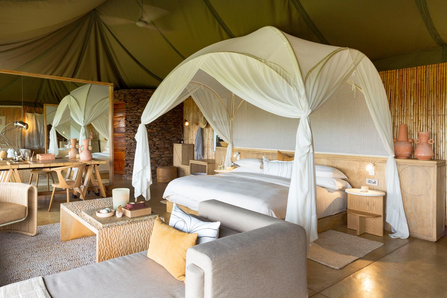 Tent interiors at Faru Faru with contemporary, clean-cut designs and a domed mosquito net enclosing the bed