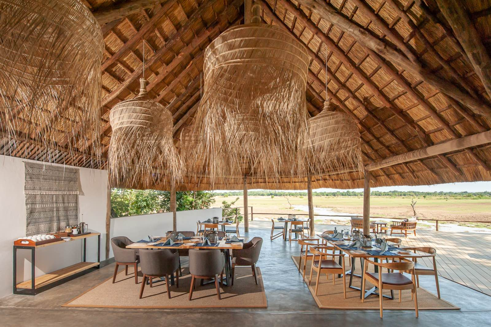 A dining area under thatch with soft furnishings and African accents