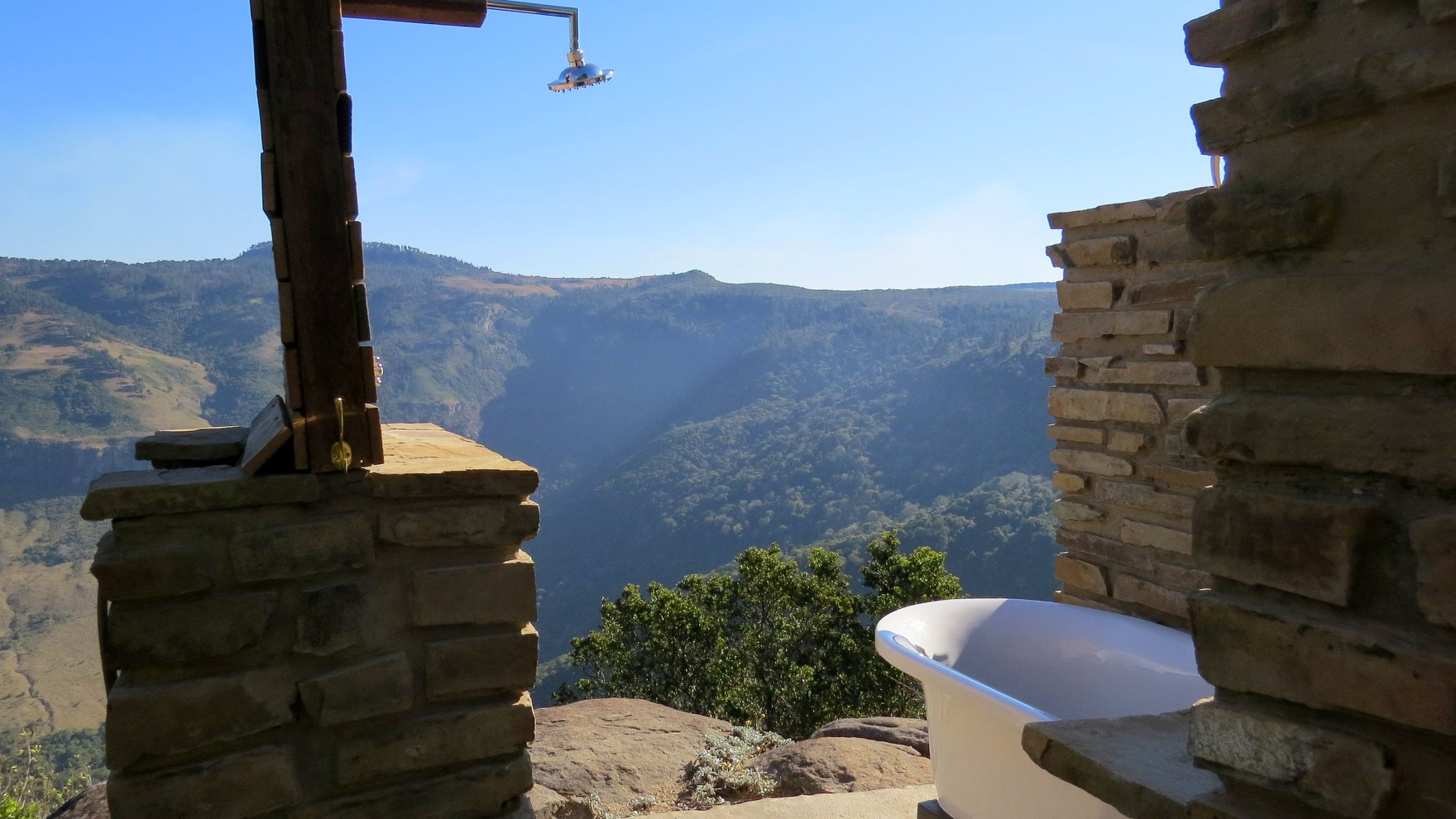 An outdoor bathroom with views of the Hogsback mountains and cliffs