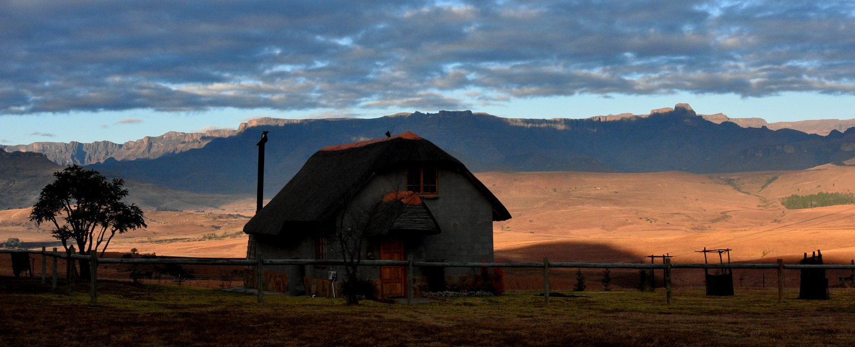 Rustic cottages at Berghouse with a backdrop of the Drakensberg